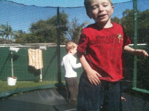 Marcus and his best friend Cohan jumping with soft green Blue Couch under the trampoline.